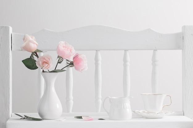 Pink roses on vintage wooden white shelf Premium Photo