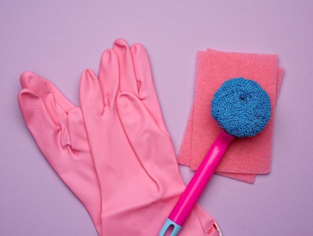Розовые резиновые перчатки для чистки, кисти на фиолетовом фоне, плоская планировка Premium Фотографии