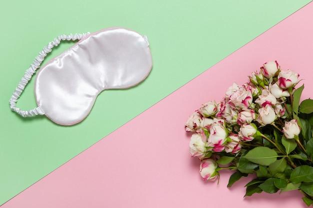 ピンクのシルクスリープマスク、パステルカラーの2色の背景に小さなバラの花束 Premium写真