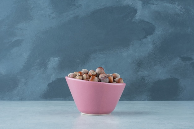 A pink small plate full of nuts on marble background. high quality photo Free Photo