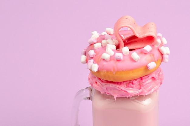 Розовый клубничный коктейль с зефиром и конфетами. Premium Фотографии