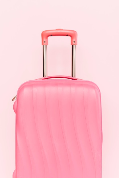 Pink suitcase for travelling against pink background Free Photo