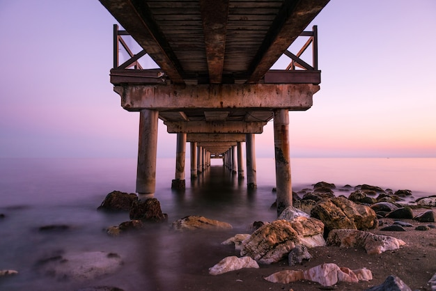 Pink sunset as seen from below an old wooden jetty on a beach in the costa del sol in marbella. Premium Photo
