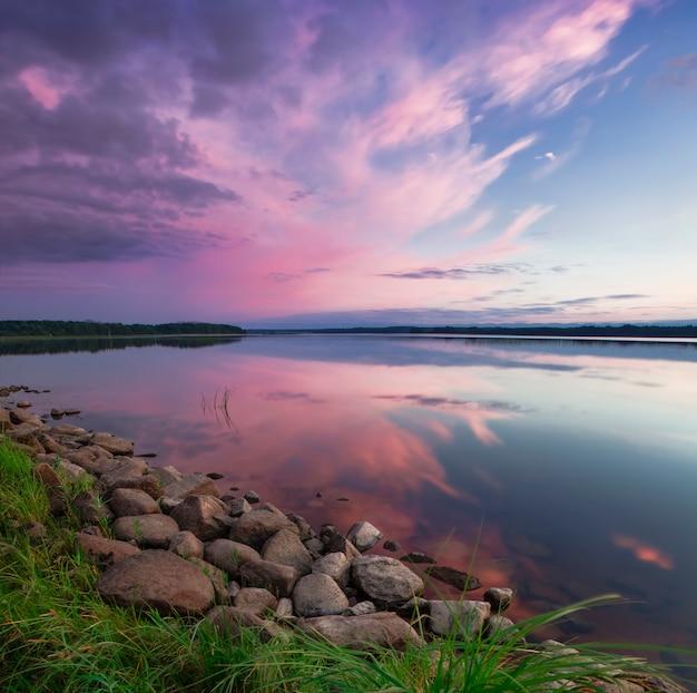 Розовый закат на озере. вечернее голубое небо отражается Premium Фотографии