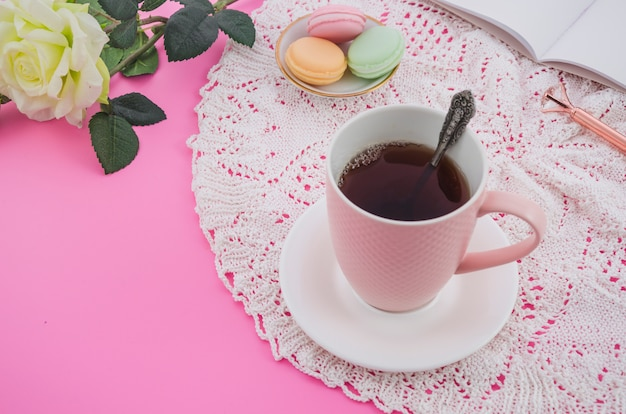 Pink tea cup with macaroons on lace tablecloth against pink background Free Photo