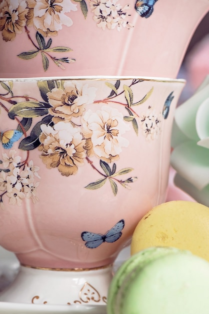 Pink tea cups with floral ornament and macaroon sweets Premium Photo