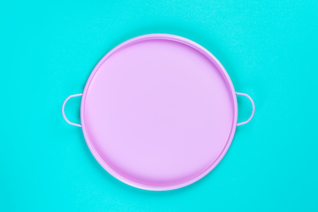 Pink tin circle tray on blue paper background, top view with copyspace for your design, frame. still life composition. Premium Photo