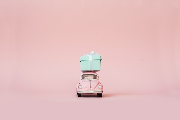 Pink toy retro model car delivering gift box on pink background Premium Photo