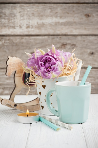 Pink tulips, blue cup, straws, lit candle and rocking horse Premium Photo