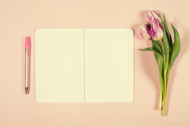 Pink tulips bouquet and open notebook Premium Photo