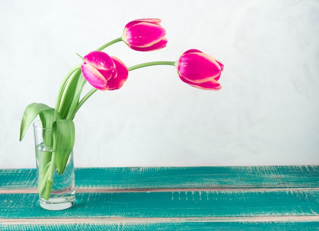 Pink tulips in glass vase on table Free Photo