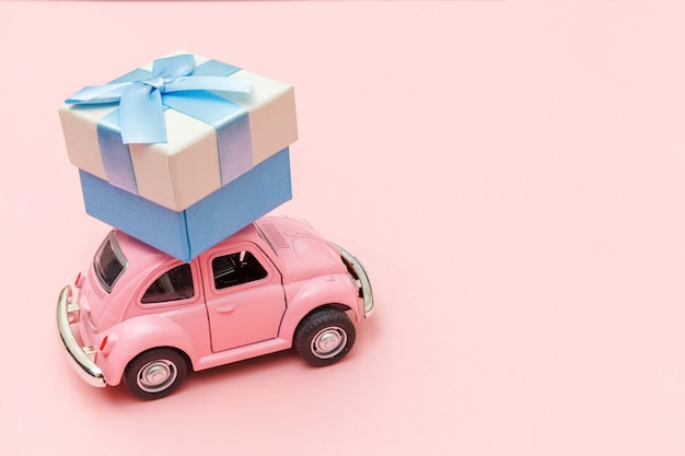 トレンディなパステルピンクの背景に分離された屋根の上のギフトボックスを提供するピンクのヴィンテージレトロなおもちゃの車 Premium写真