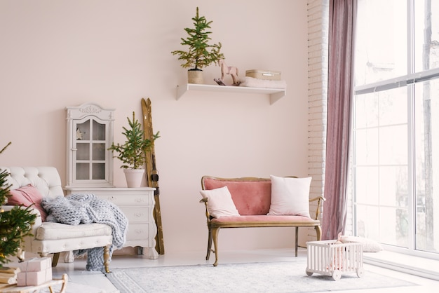 A pink vintage sofa with pillows stands near the window in the living room or children's room, decorated for christmas or new year, in the house. minimalistic interior design Premium Photo