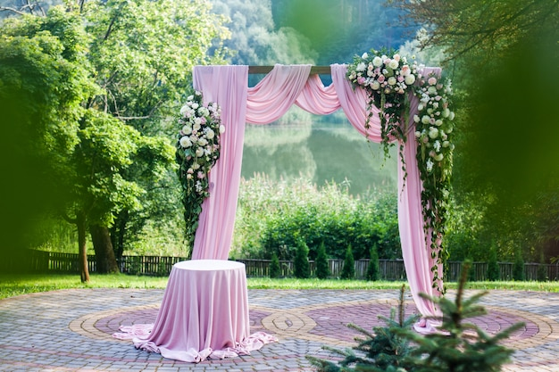 Pink wedding arch with floral white and pink decorations outside in summer Premium Photo