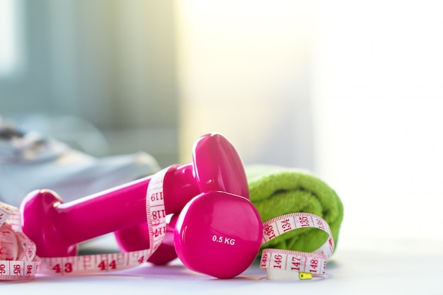 Pink weights, a tape measure and a towel Free Photo