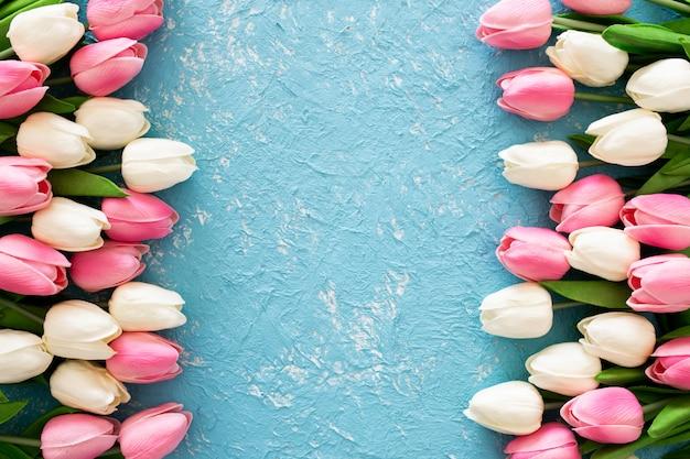 Pink and white tulips on blue grunge background Free Photo