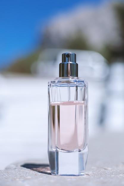 Розовый женский парфюм на синем Premium Фотографии