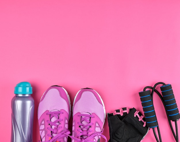Pink women's sneakers, a bottle of water, gloves and a jump rope for sports Premium Photo