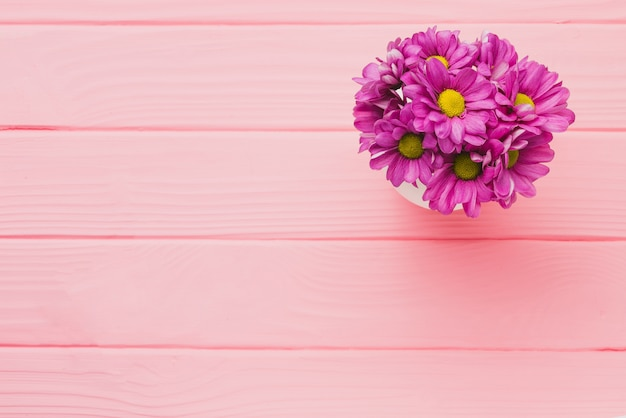 pink wooden background with purple flowers photo free