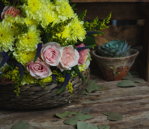 Pink and yellow flowers combination inside a bamboo vase. Free Photo