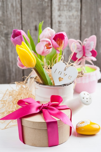 Pink yellow tulips on rustic wooden background Premium Photo