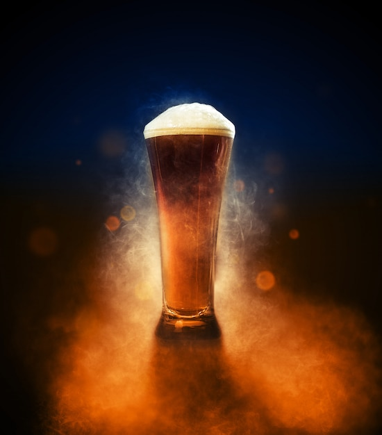 Pint beer with smoke, particles and back light product shot Premium Photo