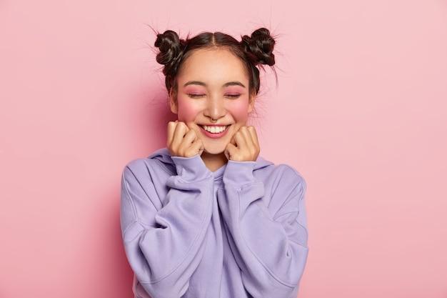 두 개의 빗질 한 머리 만두를 가진 핀업 일본 여성은 뺨을 만지고 피부가 매끄럽고 생생한 장밋빛 화장을하고 코를 뚫고 스웨트 셔츠를 입고 긍정적으로 미소를 짓고 분홍색 배경 위에 격리됩니다. 무료 사진