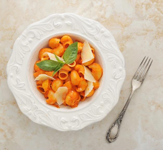 Pipe rigate pasta with cheese, basil Premium Photo