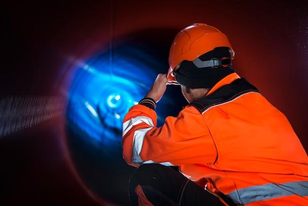 Строитель трубопровода в светоотражающей защитной униформе проверяет трубу для распределения природного газа Бесплатные Фотографии