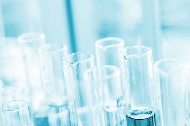A pipette dropping sample into a test tube,abstract science background Premium Photo