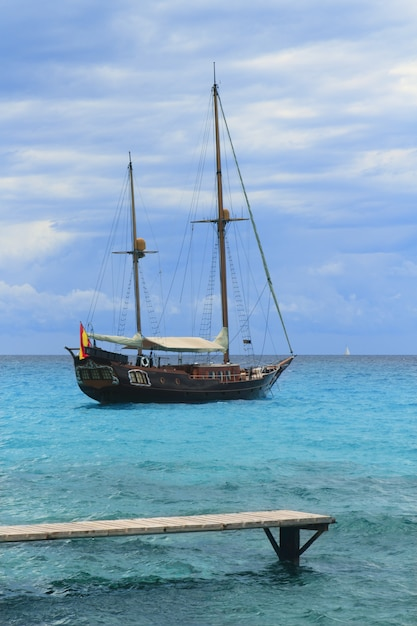Pirates inspired wood sailboat anchored turquoise Premium Photo