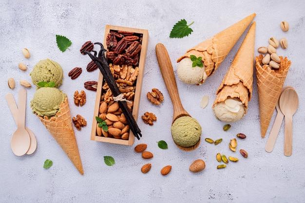 白い石の背景にミックスナッツの設定でボウルにピスタチオとバニラのアイスクリーム。 Premium写真