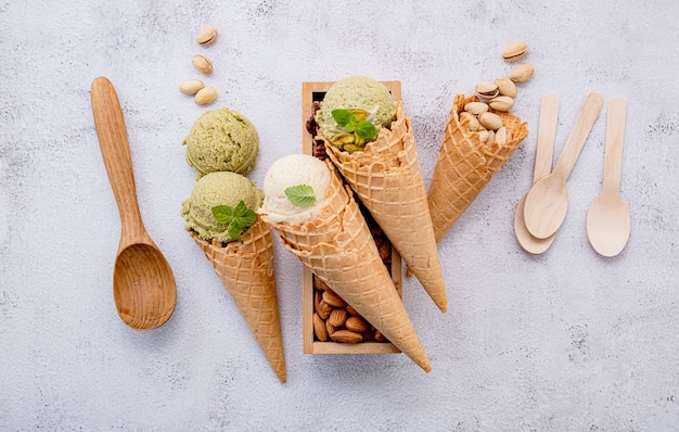 Фисташковое и ванильное мороженое в миске со смешанными орехами на белом фоне Premium Фотографии
