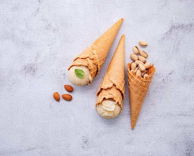 Фисташковое и ванильное мороженое в рожках с ореховой начинкой на белом фоне Premium Фотографии
