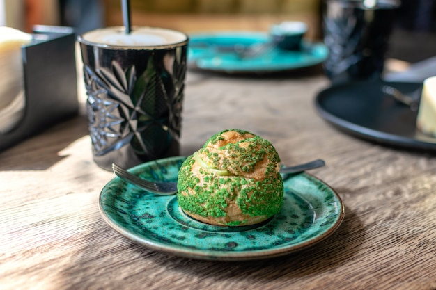 Pistachio eclair, profiterole in glaze Premium Photo