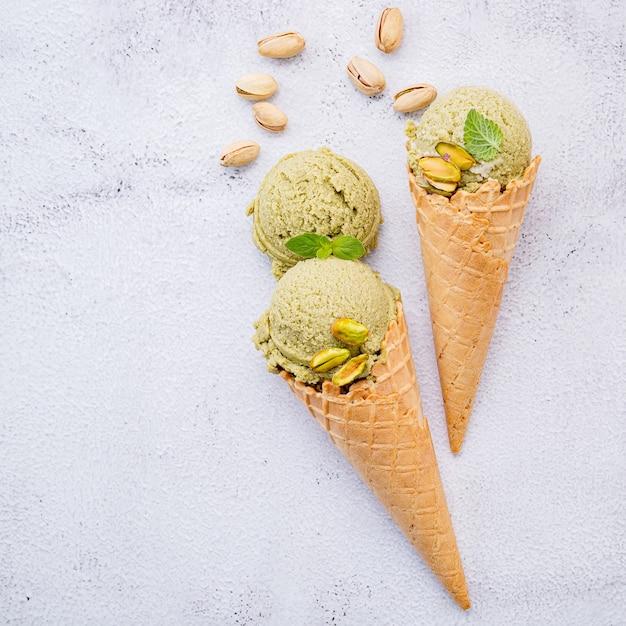 白い石の背景にピスタチオナッツのセットアップとコーンのピスタチオアイスクリーム。 Premium写真