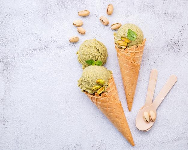 Фисташковое мороженое в конусах с фисташковыми орехами на белом фоне. Premium Фотографии