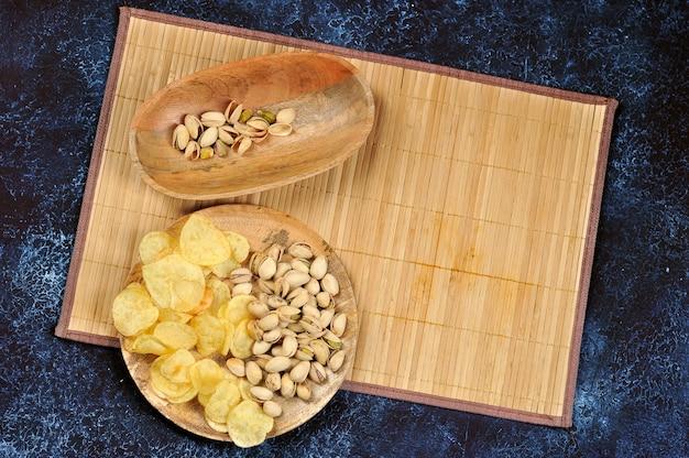 Фисташки и чипсы на деревянной тарелке на синем фоне Premium Фотографии