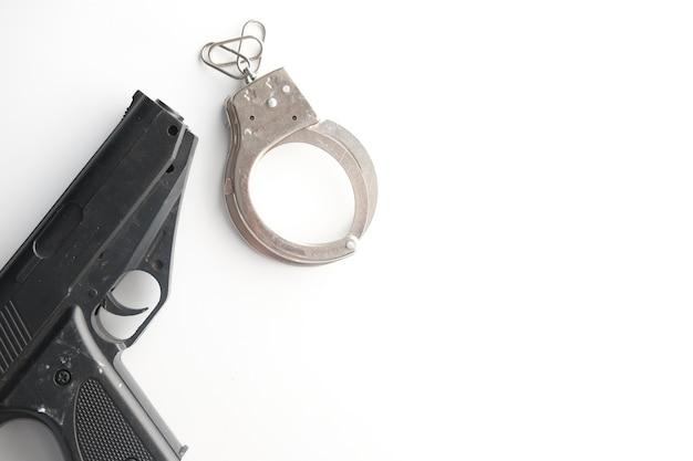 コピースペースと白い背景の上のピストルと手錠。 Premium写真