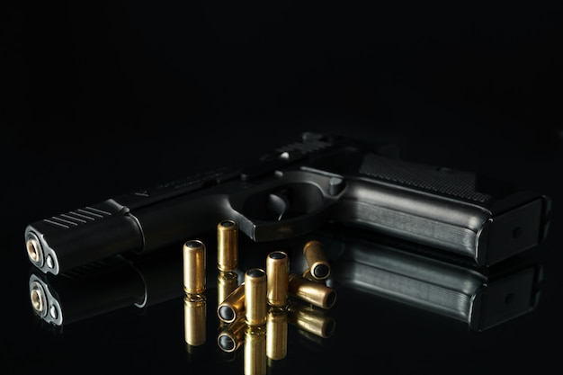 Pistol and bullets on mirror table against black Premium Photo