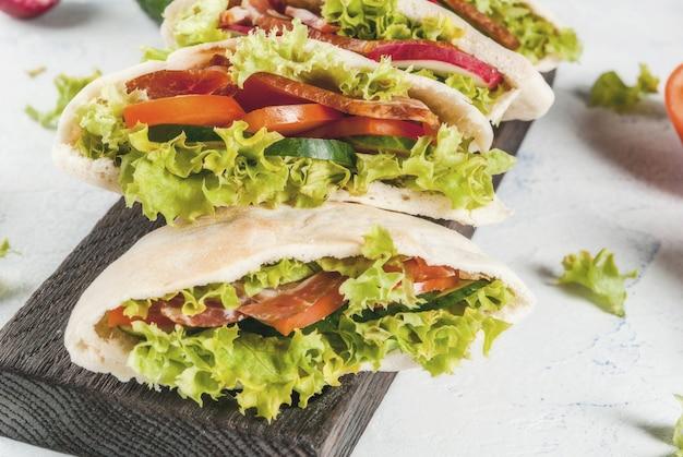 Pita bread sandwich with fresh vegetables on a light concrete table Premium Photo