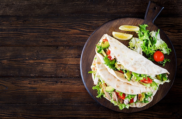 Pita bread sandwiches with grilled chicken meat, avocado, tomato, cucumber and lettuce served on wood Premium Photo