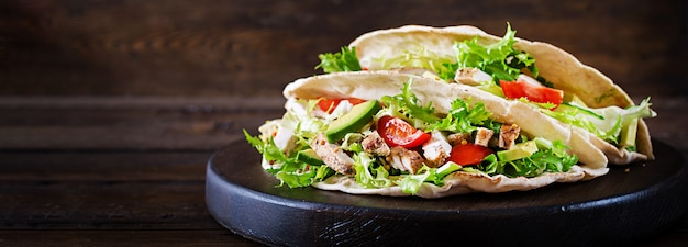 Pita bread sandwiches with grilled chicken meat, avocado, tomato, cucumber and lettuce served on wooden table Free Photo