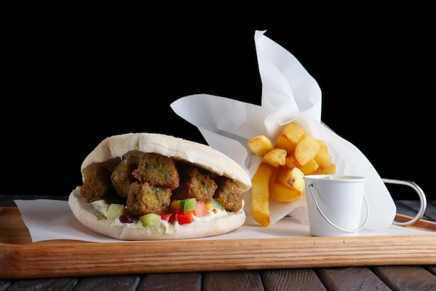 Pita bread with falafel, vegetables and fried potatos on wooden plate Premium Photo