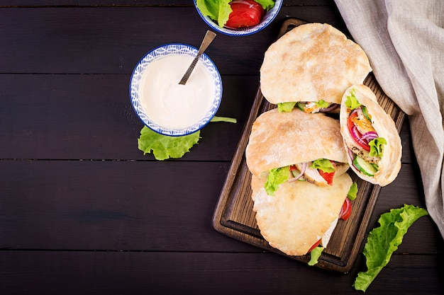 Pita stuffed with chicken, tomato and lettuce on wooden, middle eastern cuisine, top view Premium Photo