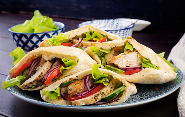 Pita stuffed with chicken, tomato and lettuce on wooden, middle eastern cuisine. Premium Photo