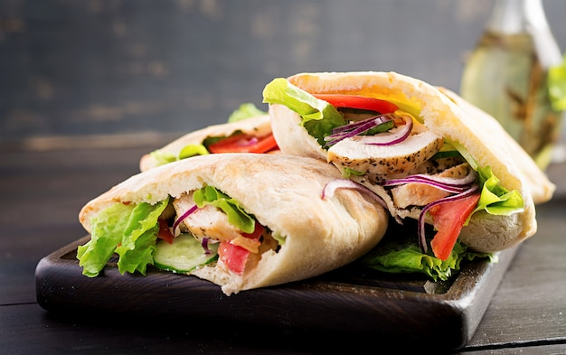 Pita stuffed with chicken, tomato and lettuce on wooden table. middle eastern cuisine. Free Photo