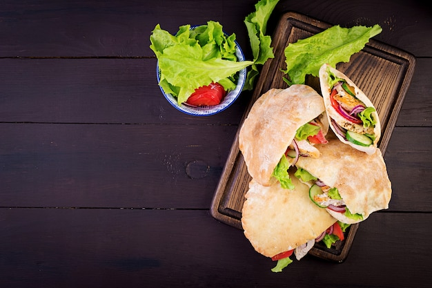 Pita stuffed with chicken, tomato and lettuce Free Photo