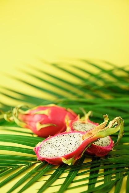 熱帯の緑のヤシの葉の上のpitahayaまたはドラゴンフルーツ。ポップアートデザイン、創造的な夏のコンセプト。 Premium写真