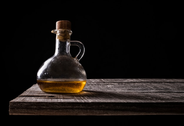 Кувшин оливкового масла на старой древесине на черном фоне Premium Фотографии